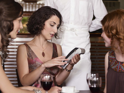 Woman paying waiter at restaurant