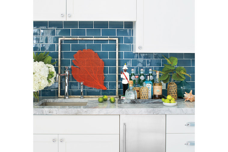 """A vibrant wet bar is tucked into the hall on the second floor, which is composed of the two guest bedrooms. """"I wanted to add in an element that brings more functionality to the deck, and really draws people upstairs,"""" says Howard. The deep blue..."""