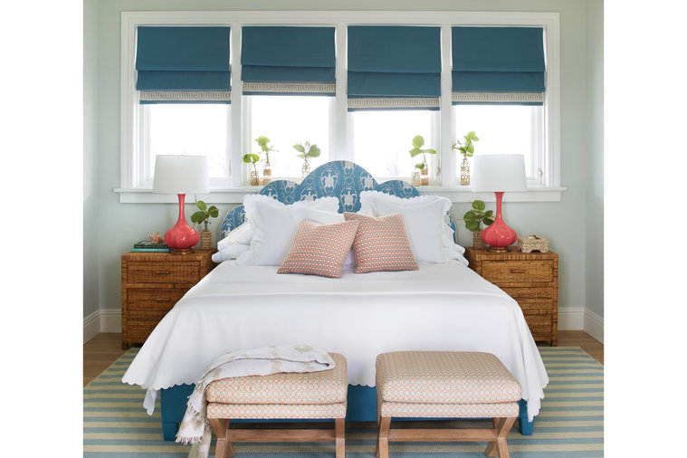 """""""We call this 'the turtle room,'"""" says Howard of the artful likenesses of the sea creatures climbing the headboard. """"A pattern like this is a great tool when you want to keep the design pretty simple."""" Solid blue Roman shades and coral lamps,..."""