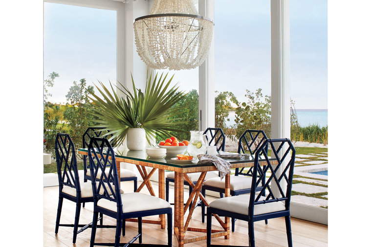 """In the open dining room, Howard paired new, painted bamboo dining chairs with a vintage rattan-wrapped table he found at a shop in Palm Beach. """"I always bring plenty of older pieces to new houses to layer in character,"""" he says. A beaded shell..."""