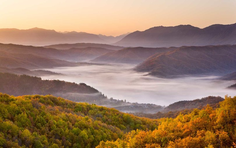 Looking down onto the little Zagorian village of Kipi on a misty morning in Autumn, just after sunrise, Epirus, Greece, Europe