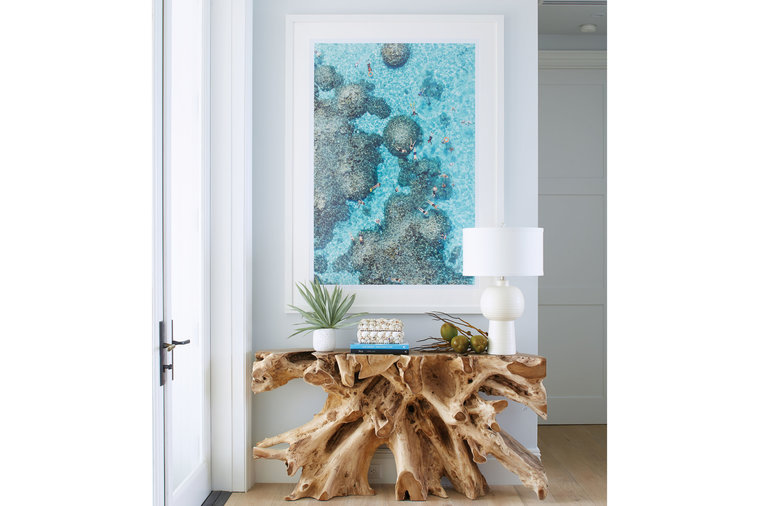 "Just inside the front door hangs an aerial photo of a reef in Bora Bora. ""The water in the art is the exact same color as in the Bahamas,"" says Howard, noting that he wanted to amplify the connection to the ocean, which is visible from the entry...."