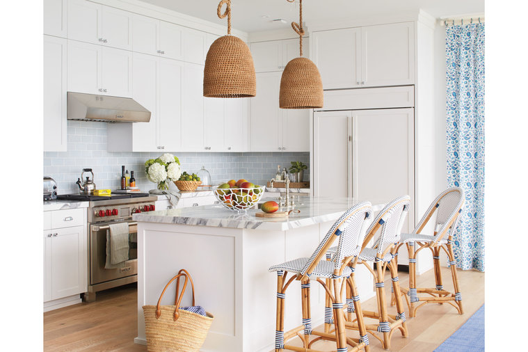 """Howard took a quiet, somewhat restrained approach to the kitchen. """"In a house where 50 percent of the walls are glass, you don't need surfaces to be too shimmery,"""" he says. Instead, he emphasized texture, choosing woven rattan lighting, French..."""