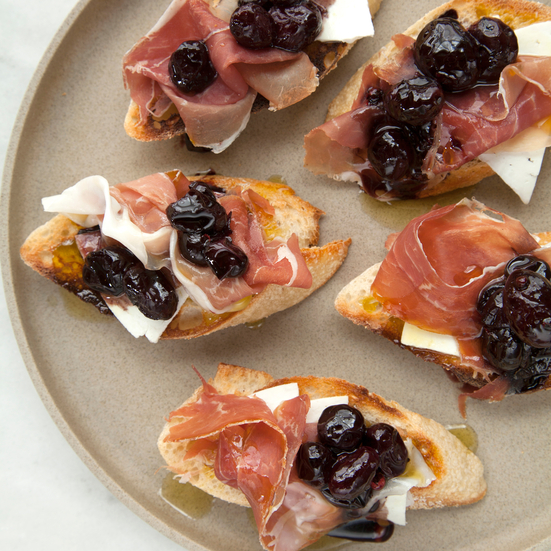 Crostini with Stewed Black Grapes, Prosciutto and Ricotta Salata