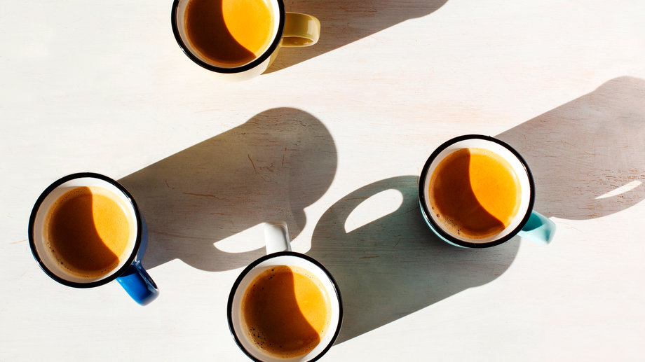 Four cups of Espresso on a table back lit by the sun casting a long shadow